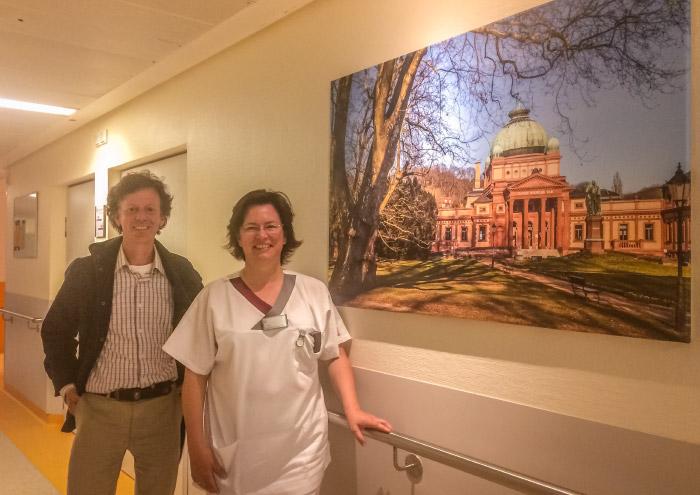 """Frau Post und Christian in der Wicker Klinik, sein Motiv """"Kaiser-Wilhelms-Bad"""" auf der Station"""